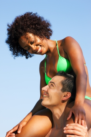 Couple in love - Woman of color in bikini sitting on her man's shoulders under blue sky - summer and fun