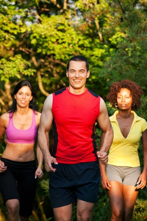 Group of friends exercising - man and two women jogging outdoors in beautiful evening light