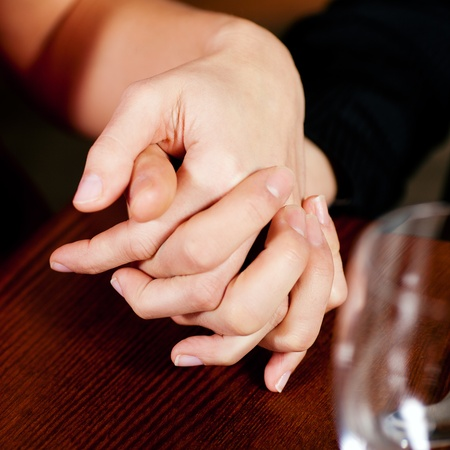 Couple, just hands to be seen, is holding hand while waiting for their food and drinks in a restaurant