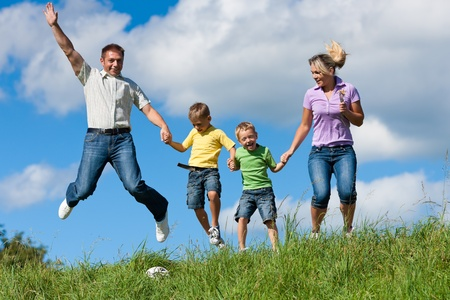 Foto de Happy family with children jumping in a meadow in summer - Imagen libre de derechos