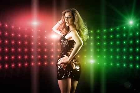 Photo for Beautiful young girl or woman dancing in a club disco to the music, lots of lights visible - Royalty Free Image