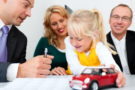 Family with their consultant  assets, money or similar  doing some financial planning - symbolized by a toy car they are holding in their hand
