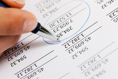 Man  only hand to be seen, presumably an accountant  working on a document with numbers