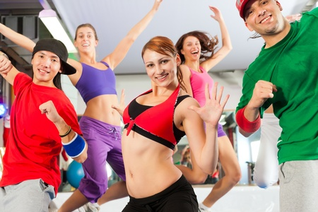Fitness - Young people doing Zumba training or dance workout in a gym