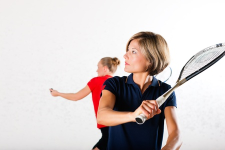 Two women playing squash as racket sport in gym, it might be a competition