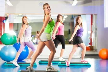 Foto de Fitness - Young women doing sports training or workout with stepper in a gym - Imagen libre de derechos