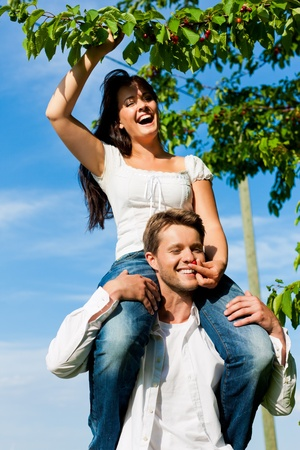 Happy couple eating cherries in summer in a garden, he is carrying her on his shoulders