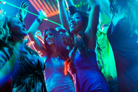 Photo pour Group of party people - men and women - dancing in a disco club to the music - image libre de droit
