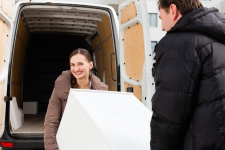 Young couple loading furniture into a moving truck, it is a fridge