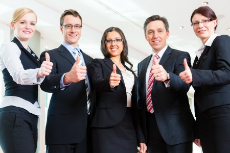 Business - group of businesspeople posing for group photo in office showing thumbs up
