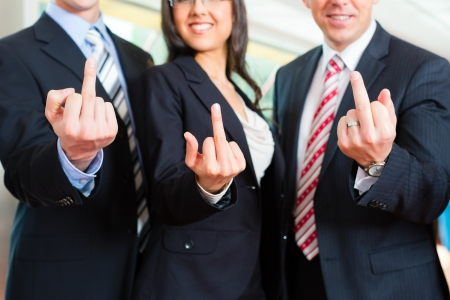 Business - group of businesspeople posing for group photo in office showing the finger
