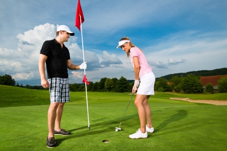 Young sportive couple playing golf on a golf course, she is putting at the green