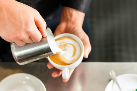 Barista making cappuccino in his coffeeshop or cafe, close-up