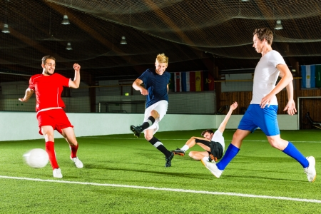 Men team playing football or soccer indoor and trying to score a goal