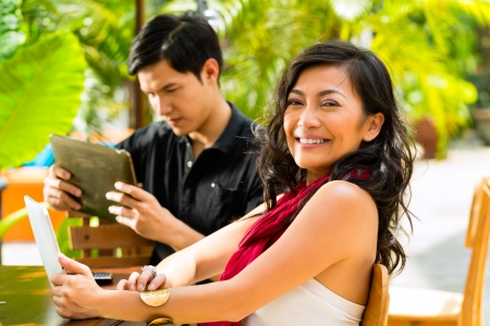 Asian woman and man are sitting in a bar or cafe outdoor and are surfing the internet with a tablet computer