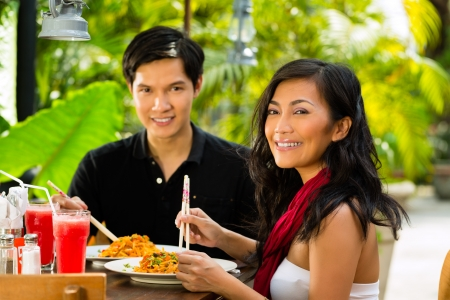 Asian man and woman in restaurant eating their food with chopsticks