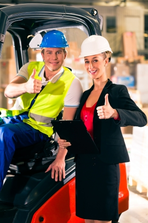 Forklift driver and female super visor with clipboard at warehouse of freight forwarding company - thumbs up
