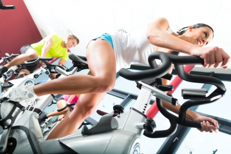 Foto de Young People - group of women and men - doing sport Spinning in the gym for fitness - Imagen libre de derechos