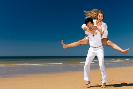 Photo pour Playful couple on the ocean beach enjoying their summer vacation, the man is carrying the woman piggyback - image libre de droit