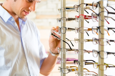 Photo pour Young man at optician with glasses, he might be customer or salesperson - image libre de droit