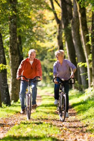 Senior Man and woman exercising with bicycles outdoors, they are a couple