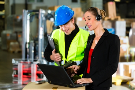 Teamwork - warehouseman or forklift driver and female supervisor with laptop, headset and cell phone, at warehouse of freight forwarding company - a forklift is in Background