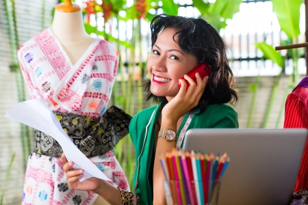 Freelancer - Fashion designer working at home on a design or draft, she uses a mobile phone, to talk with a client