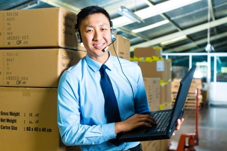 Foto de Young man in a suit with headset and laptop in a warehouse, he is from the Customer Service - Imagen libre de derechos