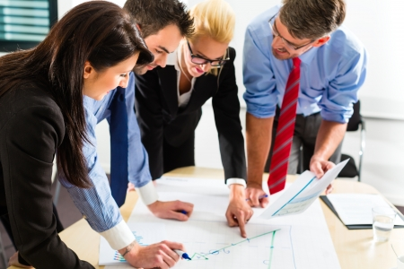 Photo pour Business - Four professionals in the office in business clothes when planning a strategy for the future of the business - image libre de droit