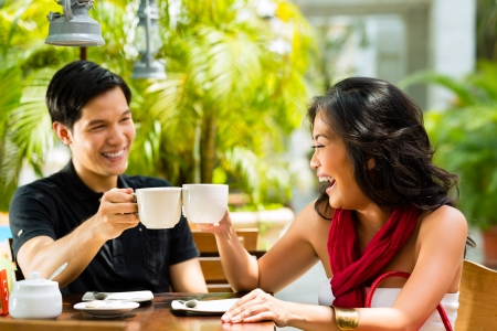 Asian man and woman in restaurant or cafe having fun drinking hot beverage
