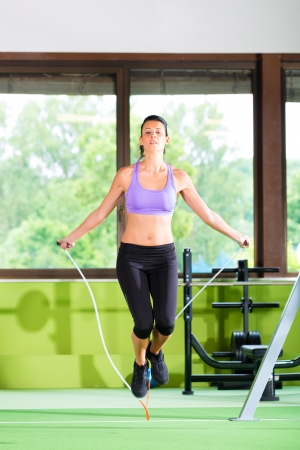 Woman jumping with rope, jumping rope in a fitness club or gym
