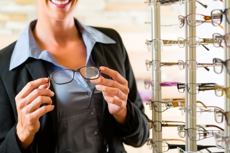 Photo pour Young woman at optician with glasses, she might be customer or salesperson - image libre de droit