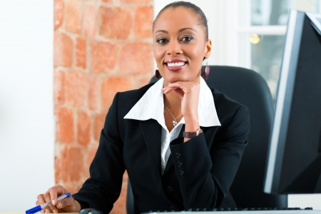 Young female lawyer or paralegal working in her office on a Computer or Pc