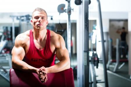 Strong man - bodybuilder or trainer standing in a gym, workout equipment is in the Background