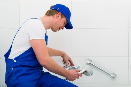 Emergency Service - Plumber or contractor repairing a not working shower in the bath