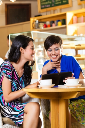 Asian female friends enjoying her leisure time in a cafe, drinking coffee or cappuccino and looking at photos or emails on a tablet computer