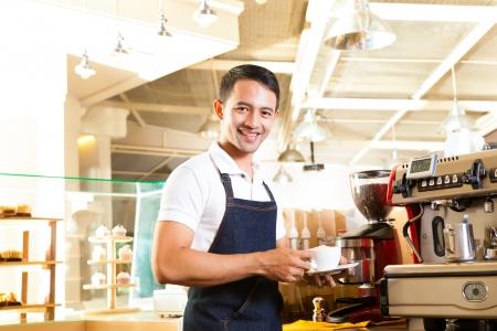 Coffeeshop - asian barista presents coffee in his shop