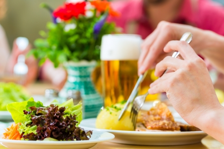 Young people in traditional Bavarian Tracht eating pork in restaurant or pub for lunch or dinner