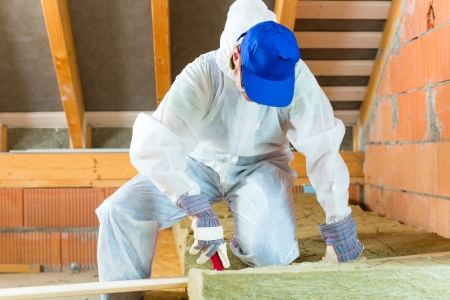 Photo pour Worker in overall is cutting insulating material with gloves and knife  - image libre de droit