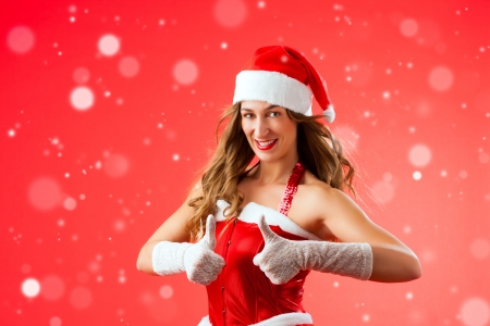 Attractive young woman in Santa Claus costume with thumbs up okay approval snow flakes on isolated red background Xmas celebration festive winter smiling happy