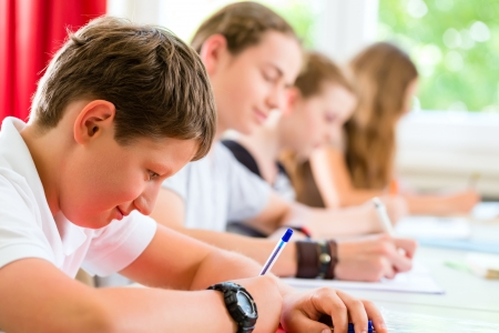 Photo pour Students or pupils of school class writing an exam test in classroom concentrating on their work - image libre de droit