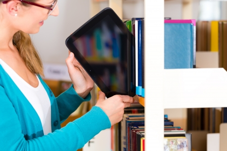 Student - young woman or girl taking a tablet computer with e-book out off the bookshelf