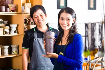 Photo pour Asian seller or souvenir dealer speaks with an Indonesian customer at a shop and shows her pottery - image libre de droit