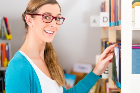 Student - young woman or girl taking a book or textbook out off the bookshelf