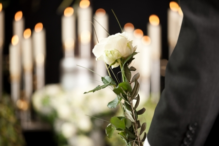 Religion, death and dolor  - man at funeral with white rose mourning the dead