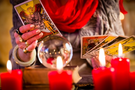 Female Fortuneteller or esoteric Oracle, sees in the future by playing her tarot cards during a Seance to interpret them and to answer questions