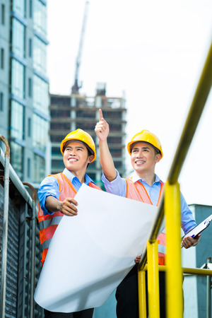 Asian Indonesian construction workers with blueprint or plan on building site