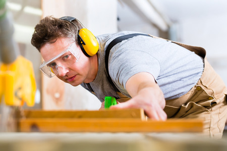 Photo pour Carpenter working on an electric buzz saw cutting some boards, he is wearing safety glasses and hearing protection for workplace safety - image libre de droit