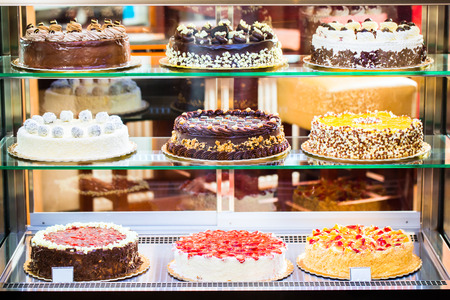 Pastry shop glass display with selection of cream or fruit cake