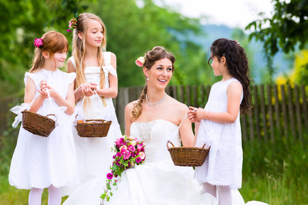 Wedding bride with flower children or bridesmaid outside at garden